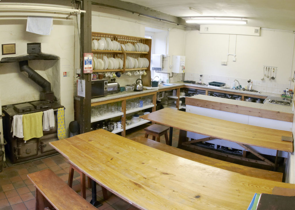 View of the rayburn, gas hobs, sinks, benches and crockery in the kitchen at Blaen-y-Nant