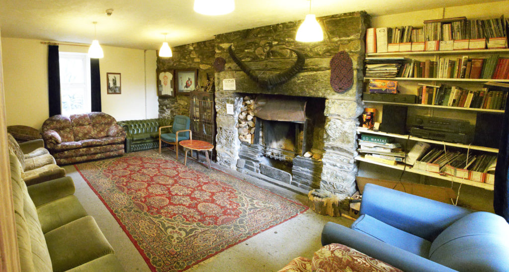 Sofas and chairs around the fireplace in the lounge area with magazines, books and games on the bookshelves